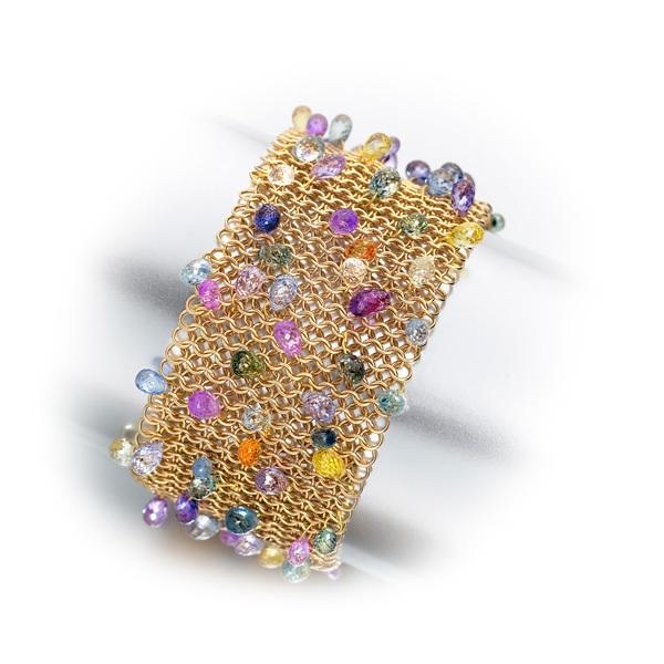 Multicolour sapphire briolletes set into an 18 carat gold mesh cuff